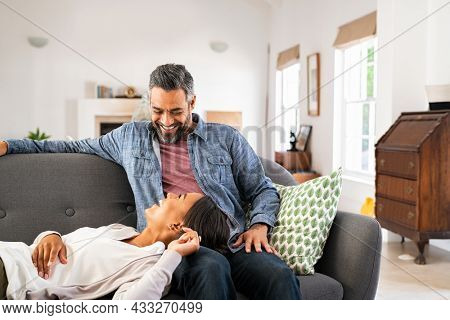 African woman lying on man's lap while talking with him on sofa at home. Happy ethnic wife lying on couch while relaxing with her husband. Mature indian man having a conversation with his wife.