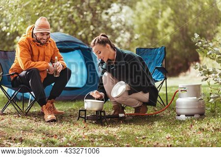 camping, tourism and travel concept - happy couple drinking beer and cooking food in pot on tourist gas burner at tent camp