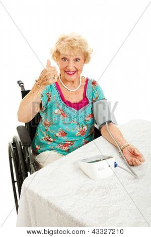 Pretty senior woman in wheelchair taking her blood pressure and giving thumbs up sign.  Isolated on white.