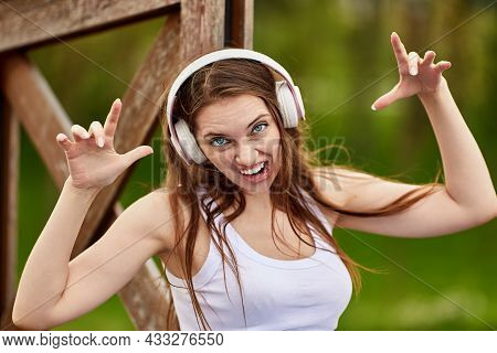 Woman In Cordless Headphones Makes Grimace Outdoors.