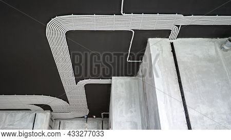 Electrical Cables And Pipes On House Concrete Ceiling. Modern Plastic Hoses And Conduits With Wires