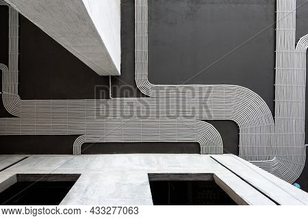 Electrical Cables And Pipes On House Concrete Ceiling Background, Plastic Hoses With Wires In Empty