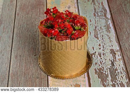 Closeup Of A Dress Cake, Wrapped In A Textured Layer Of Salted Chocolate Caramel, With Strawberries