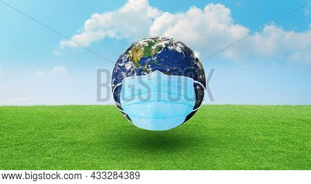 Earth Wearing A Surgeon Mask To Fight Against Corona Virus Or Covid-19 On Green Background. World Co