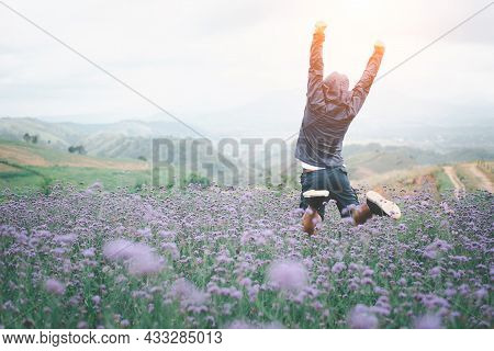 Sport And Success Concept ,hiker With Backpack Raising Hands Jumping On The Top Of A Mountain - Succ