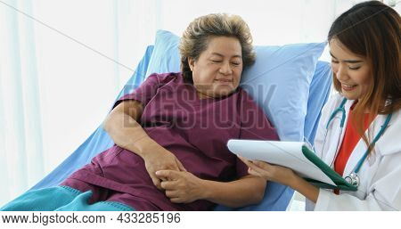 Doctor Explaining Medication To Old Woman Patient At Hospitals