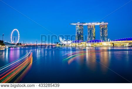 SINGAPORE, SINGAPORE - MARCH 2019: Skyline of Singapore Marina Bay at night with Marina Bay sands, Art Science museum , skyscrapers and tourist boats