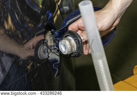 A Man Holds An Orange Canister Of Gasoline In His Hand Next To A Car With A Drain Hose Screwed On Th