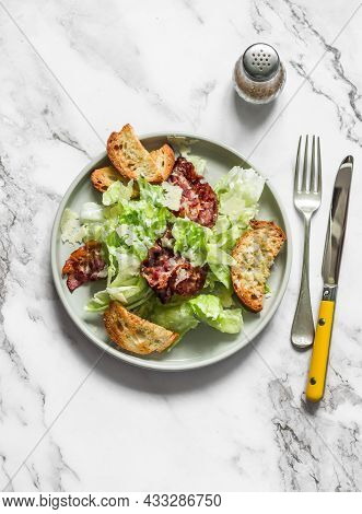Alternative Caesar Salad With Bacon On A Light Marble Background, Top View