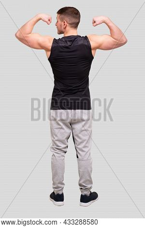 Man Showing Biceps Hands Up. Sportsman Showing Muscles. Abs, Biceps Muscles. Man Standing Isolated