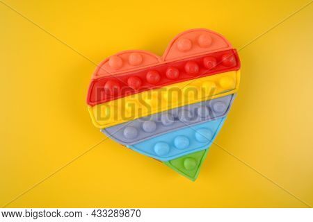 Multi-colored Gingerbread In The Form Of A Fashionable Anti-stress Toy,an Lgbt Rainbow Heart On A Ye