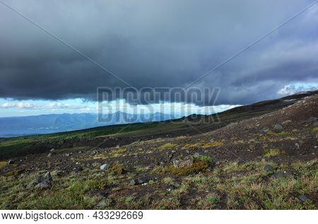 Dark slope of Villarrica volcano with sparse vegetation, low dark clouds and view of sunny mountains in distance between sky and earth, Nature background with space for text, Chile