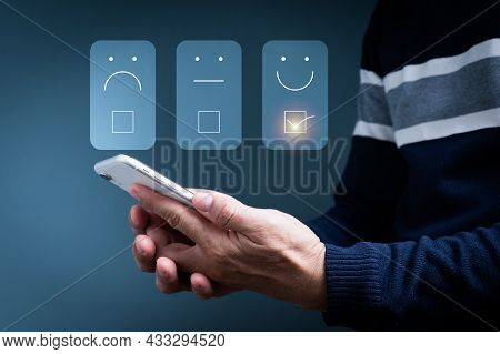 A Man Uses A Mobile Phone To Chooses A Face Smile Emoticon To Show On The Virtual Screen. The Survey