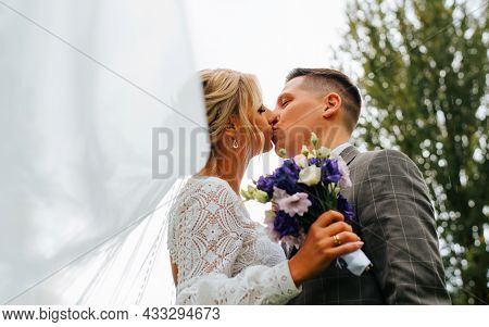 Portrait Of Newlyweds Wedding Kiss Outdoors, Groom In Suit Kissing Bride In White Dress With Veil An