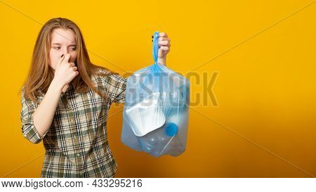 Banner Copy Space. Woman Holding A Smelly Garbage Bag On Yellow Background.