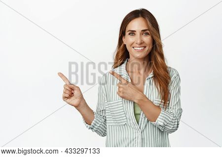 Image Of Confident, Ambitious Middle Aged Woman Smiling White Teeth, Pointing Fingers Left At Logo,
