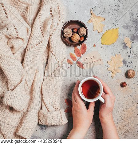 Womans Hands Holding A Cup Of Tea., Autumn Leaves On Concrete Background. Cozy Beige Sweater.