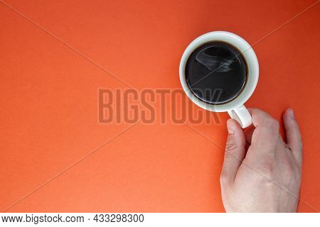 Male Hands Hold A Cup Of Hot Americano Coffee On A Bright Plain Background. Copy Space. View From Ab