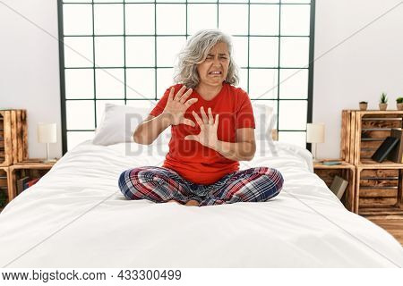 Middle age woman with grey hair sitting on the bed at home disgusted expression, displeased and fearful doing disgust face because aversion reaction. with hands raised