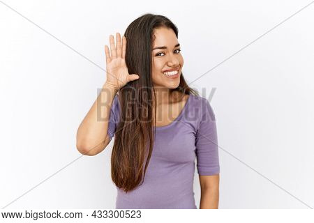 Young brunette woman standing by isolated background smiling with hand over ear listening an hearing to rumor or gossip. deafness concept.