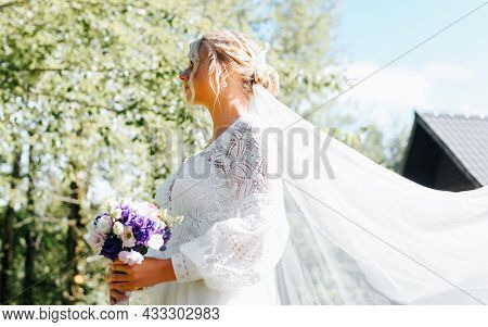 Profile Portrait Of Beautiful Stylish Blonde Bride In White Wedding Dress With Veil And Bouquet Of F