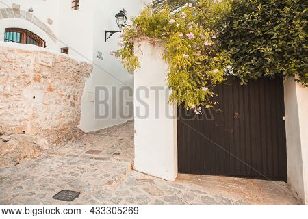 The Architecture Of The Island Of Ibiza. A Charming Empty White Street In The Old Town Of Eivissa.