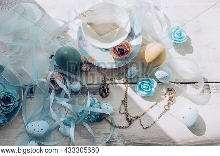 Porcelain Tea Set With Decorative Blue Organza And Atlas Ribbons Flowers And Eggs On Wooden Table