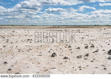 Salt-marsh With Small Black Stones And Cloudy Skies Over It Low Angle View