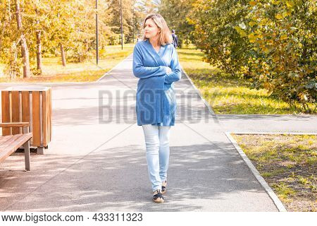 The First Cool Days. Caucasian Woman Freezing Wrapped Up In A Warm Cardigan. The Onset Of Autumn. A