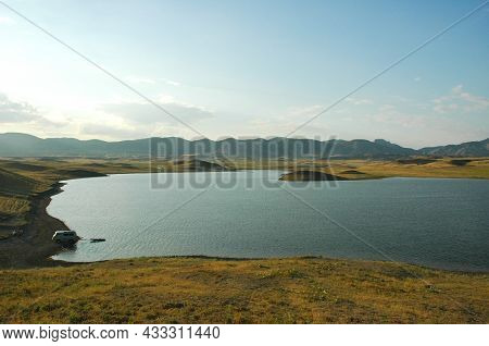 A Lake Among The Sand Hills. Beautiful Sunny View Of The Deserted Lake. Background Of Yellow-brown H