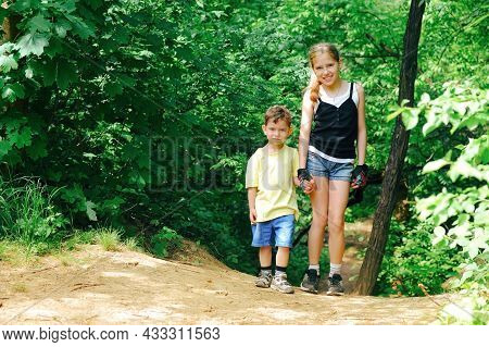 A Beautiful Young Girl And Her Brother Are Having A Rest While Walking Through The Woods. They Enjoy