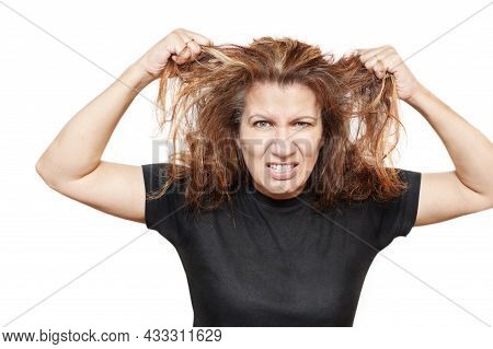 Beautiful Angry Woman On A White Background Tearing Her Hair On Her Head From Anger. She's Angry Bec