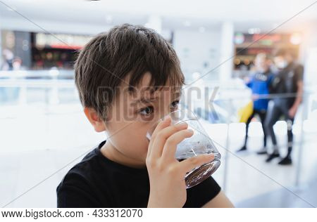 Side View Portrait Of Mixed Race Young Kid Sitting On Table Drinking Cold Drink In Restaurant, Toodl