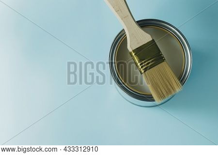 Paint Brush With Wooden Handle And Open White Paint Can On A Cyan Blue Background. Renovation Concep