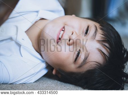 Close Up Face Of Cute Little Child Boy Lying On Carpet, Candid Shot Mixed Race Kid Playing Alone Wit