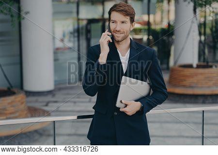 Half Length Shot Of Handsome Businessman Makes Phone Call In Roaming Using Tariffs Carries Digital D