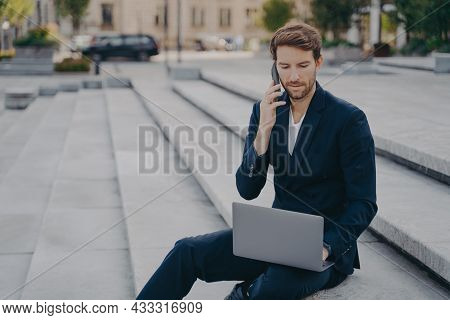 Man Executive Worker Talks On Cellphone With Business Partner Uses Modern Laptop Computer For Making