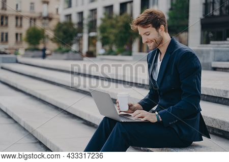 Young Satisfied Businessman In Stylish Dark Blue Suit Sitting On Stairs Near Office Center Outside W