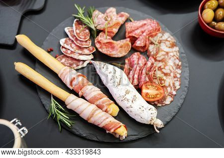 Sausage Delicacies On A Black Plate Decorated With Tomatoes And Herbs. Tasting Meat Products.