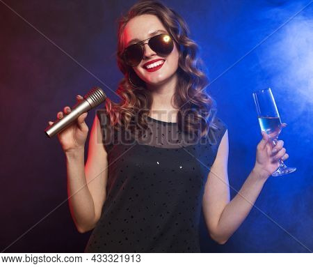 Young happy female singing into microphone at party, photo over blue background.