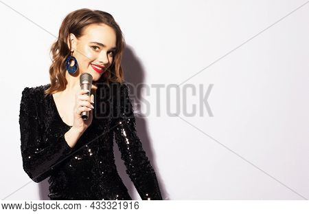 Lifestyle and party concept: Young woman in black dress with microphone.