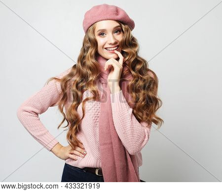 Lifestyle, emotion and people concept: Beautiful young smiling woman with long wavy hair wearing pink shirt and beret