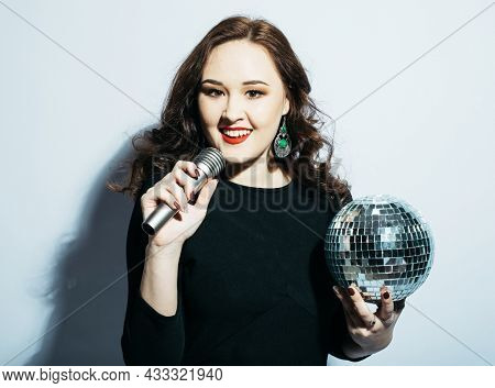 Beautiful woman holding a microphone and disco balls over white background.