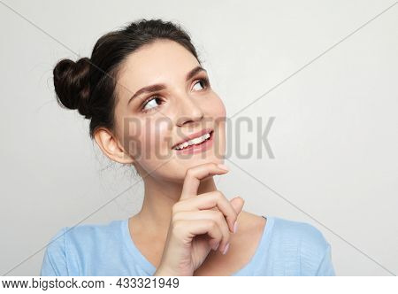 young woman dreamily looks up, ponders the future