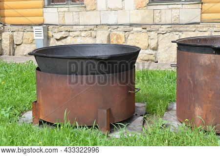 Two Large Black Metal Cast-iron Cauldrons For Pilaf On A Homemade Stand From A Large Pipe Outside On