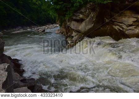 A Stormy Stream Of A Mountain River With A Foamy Waterfall Flows Between The Rocky Banks