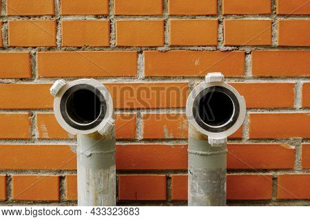 The External Pipes Of The Fire Hydrant Come Out Of The Brick Wall Of The Building To Connect The Hos