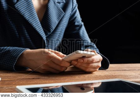 Businesswoman Using Mobile Phone At Desk. Close Up Woman Hands And Tablet Computer. Mobile Communica