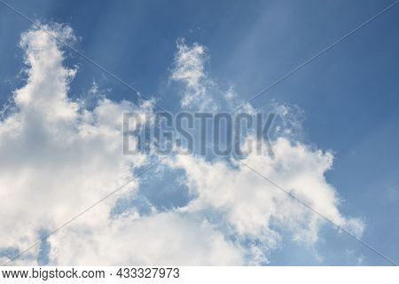 Cloud In The Sky With Shades And Radial Sunbeams Closeup Over Clear Blue Sky Diagonal Composition Wi