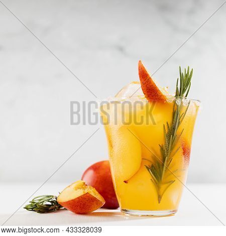 Bright Refreshing Summer Peach Alcohol Cocktail With Ice, Green Rosemary Twig, Sugar Rim, Fruit Piec